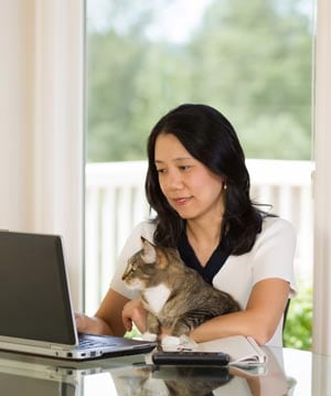Woman and cat looking at laptop