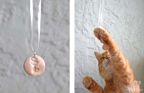 orange tabby cat assists with showing ceramic pendant