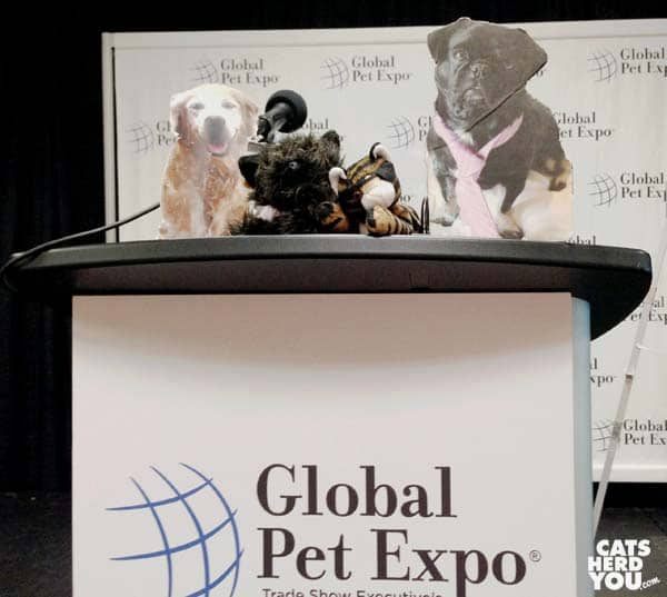 flat Sugar the Golden Retriever, plush Oz the Terrier, plush Ashton, and flat Kilo hold press conference at Global Pet Expo 2016